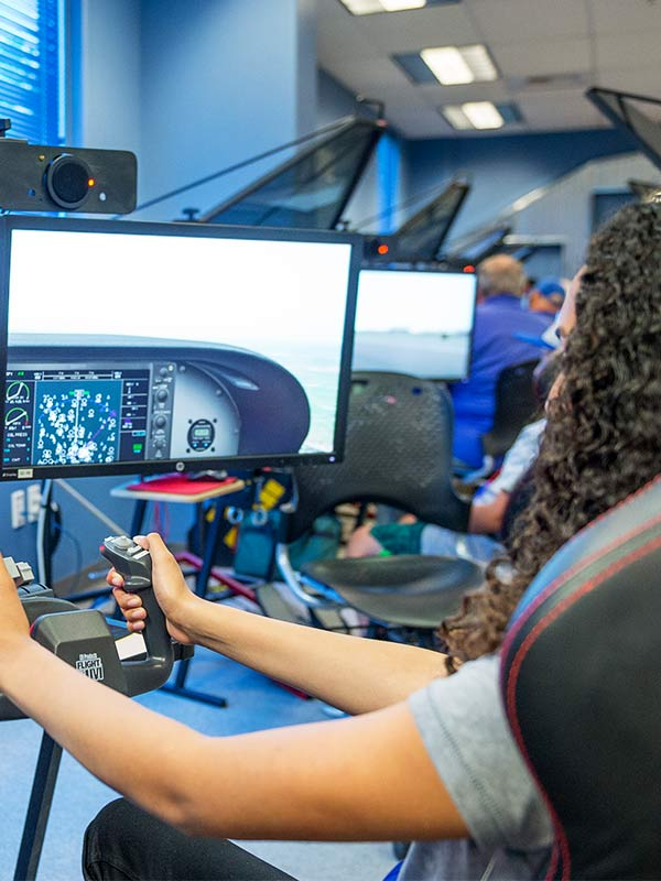 student piloting flight simulator at flight zone